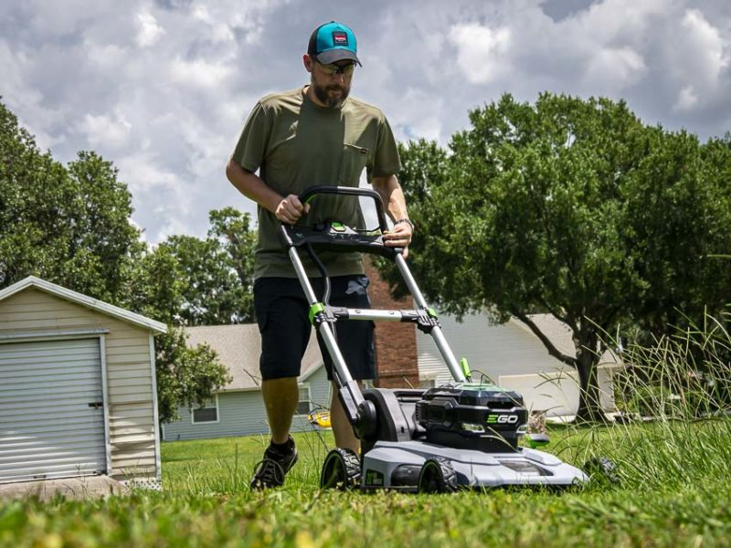 Homeowner using a battery powered lawnmower on an overcast day.